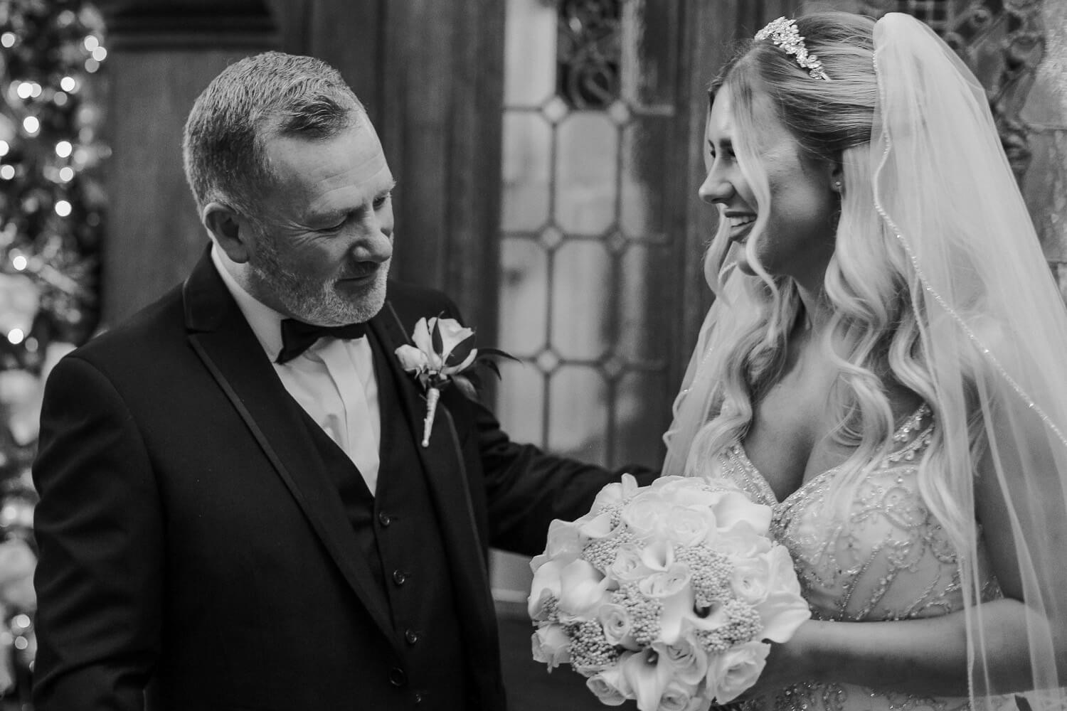Father looking at brides dress