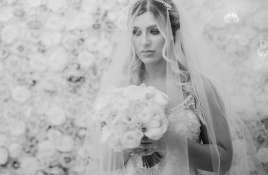Beautiful black and white portrait of bride standing in front of floral wall West Tower winter wedding