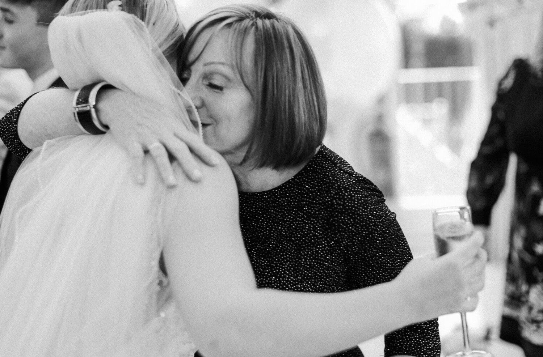 Woman warmly hugging bride