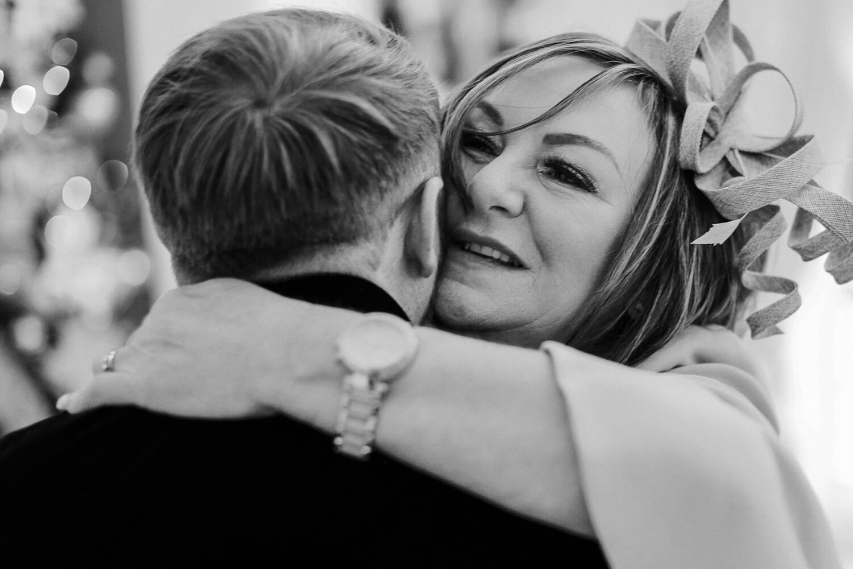 Mum hugging son at wedding