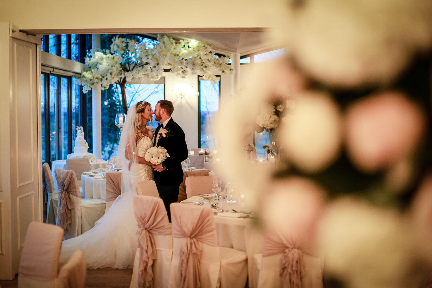 Bride and groom kissing in Ballroom at West Tower with flowers