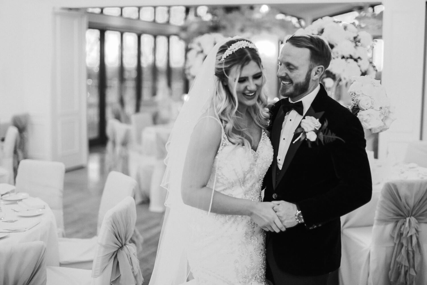 Black and white photo of bride and groom laughing in Ballroom at West tower