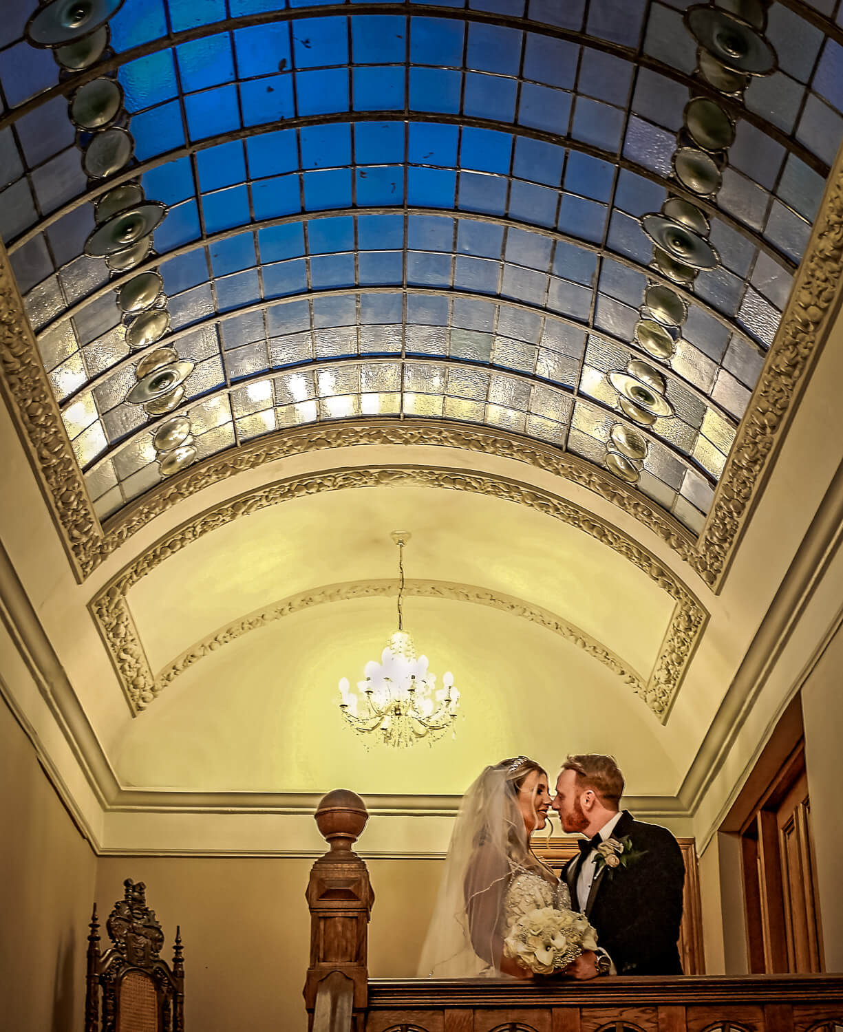 Bride and groom at top of stairs in West Tower with blue skylight