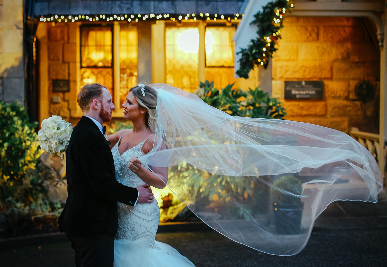 Bride and groom in front of West Tower at night with veil blowing