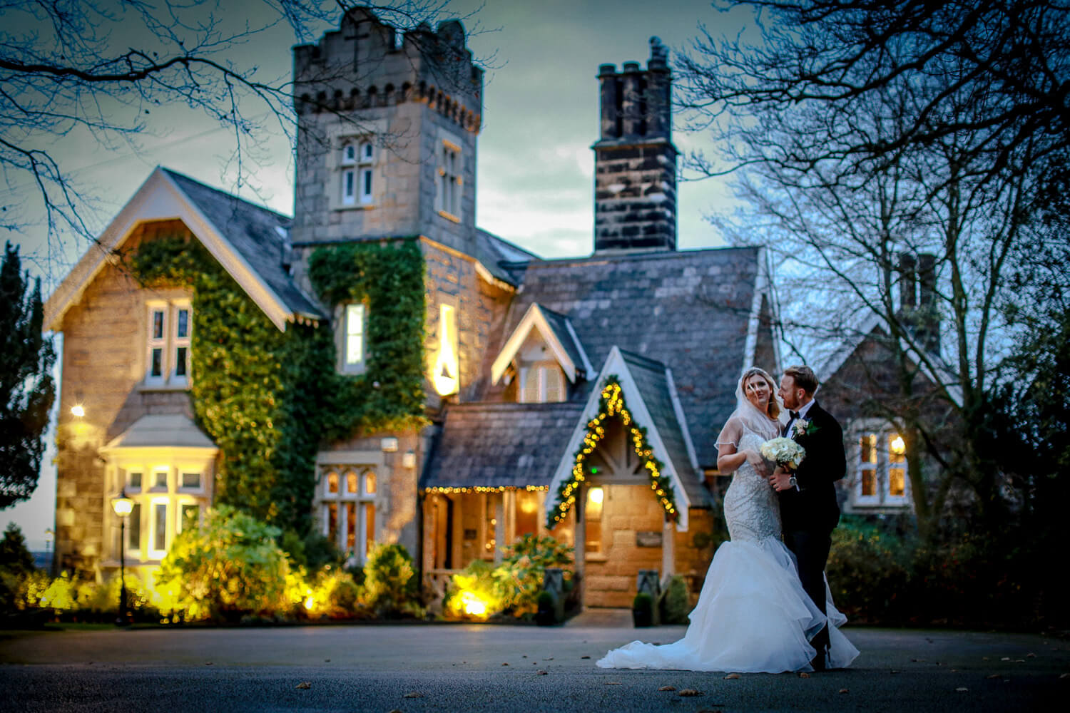 Bride and groom in front of West Tower at night
