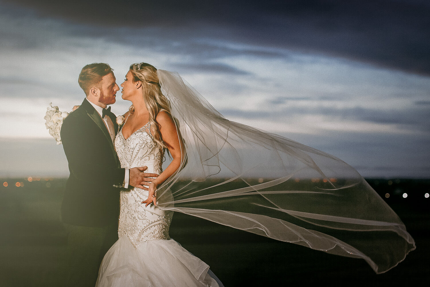 Portrait of bride and groom with blue sky sunset and veil blowing West Tower winter wedding