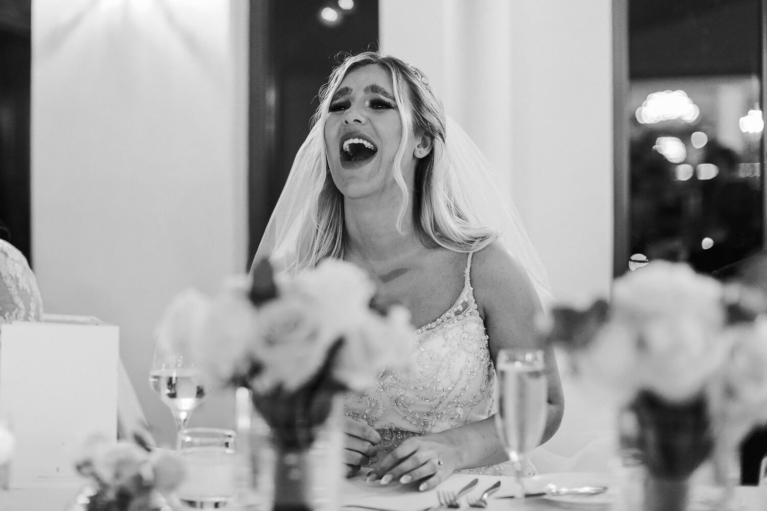 black and white photo of bride laughing during wedding speeches