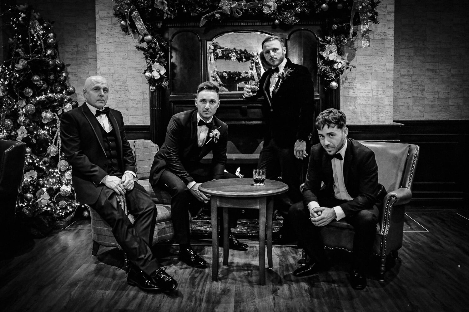 Black and white groomsman photo in leather lounge at West Tower