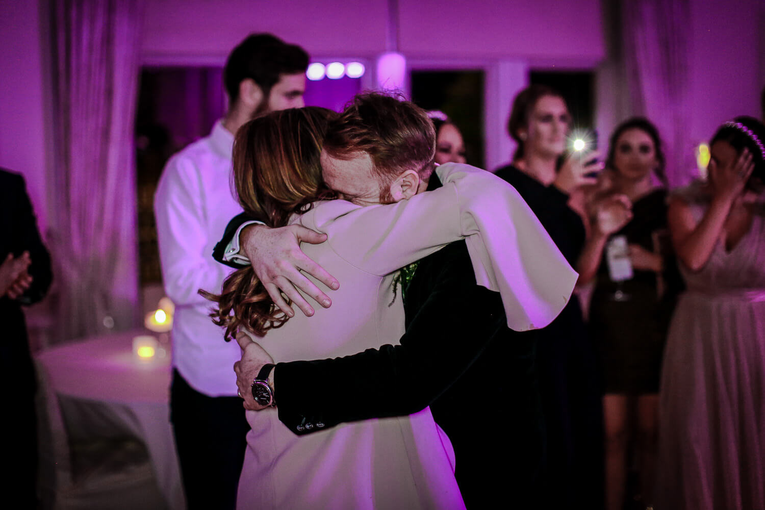 son and mum hugging on dace floor at wedding