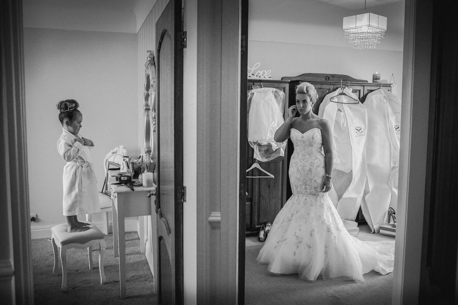 Little girl and bride getting ready on either side of wall. Documentary wedding photography