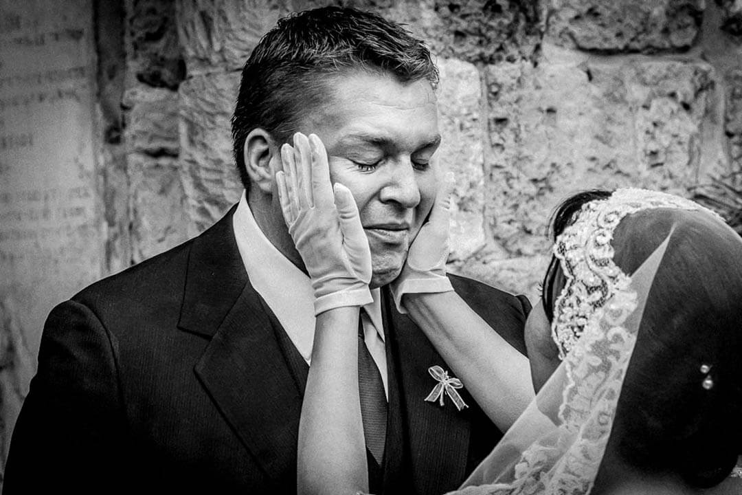emotional groom being comforted by brides hands in gloves. Your wedding and my approach to photography