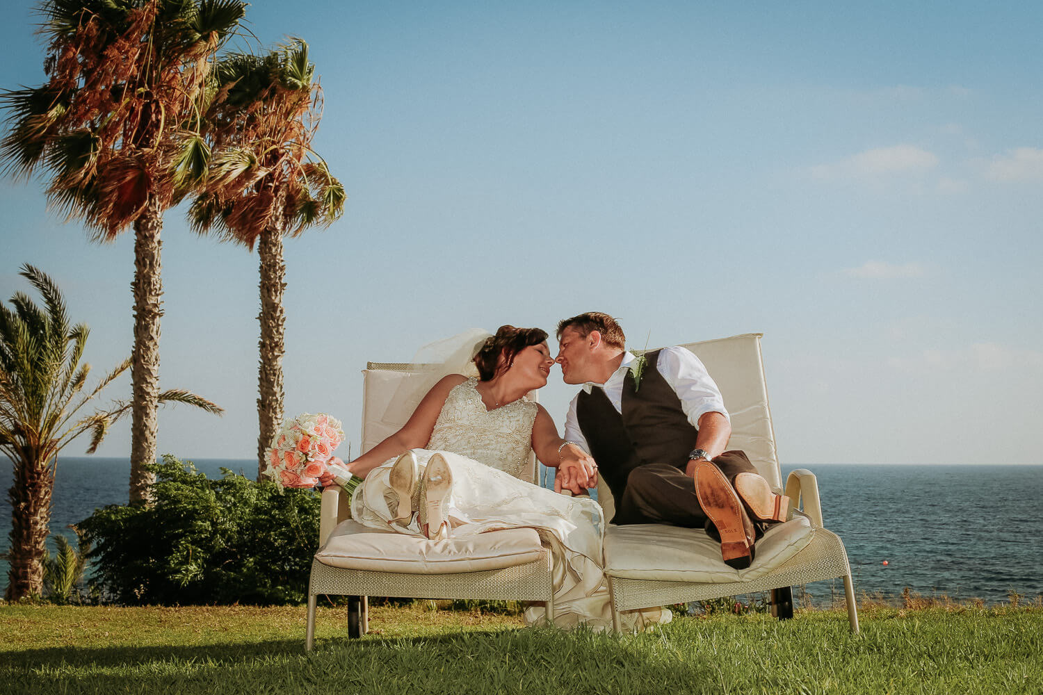 Destination wedding photography Paphos Cyprus, Bride and groom kissing sat of sun beds with palm trees and blue sky