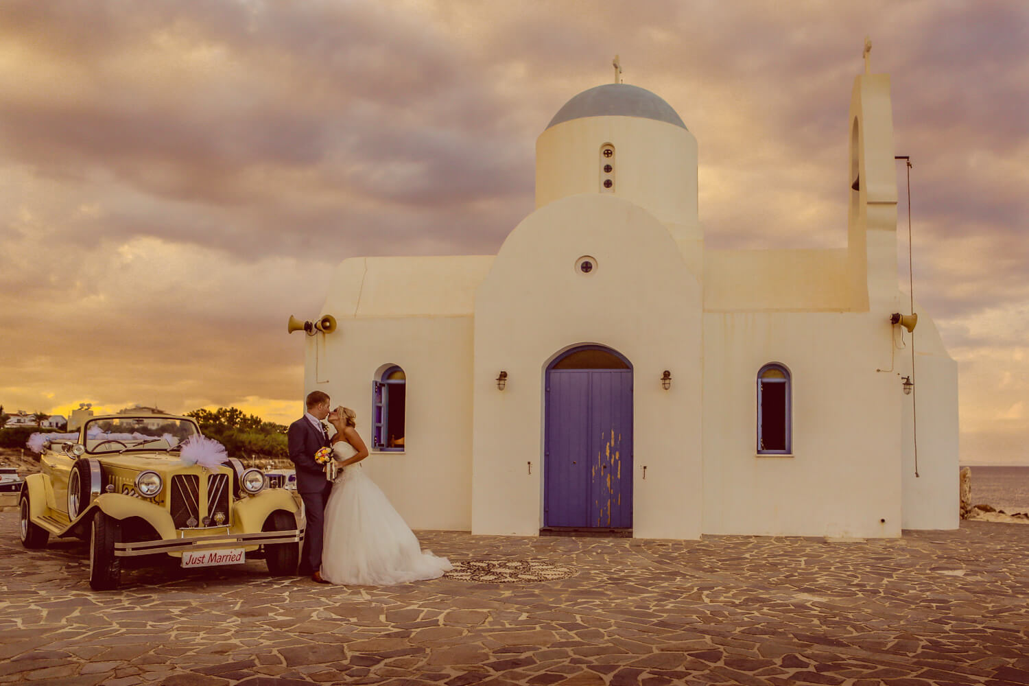 bride and groom kissing at sunset in front of little white church in Protaras Cyprus