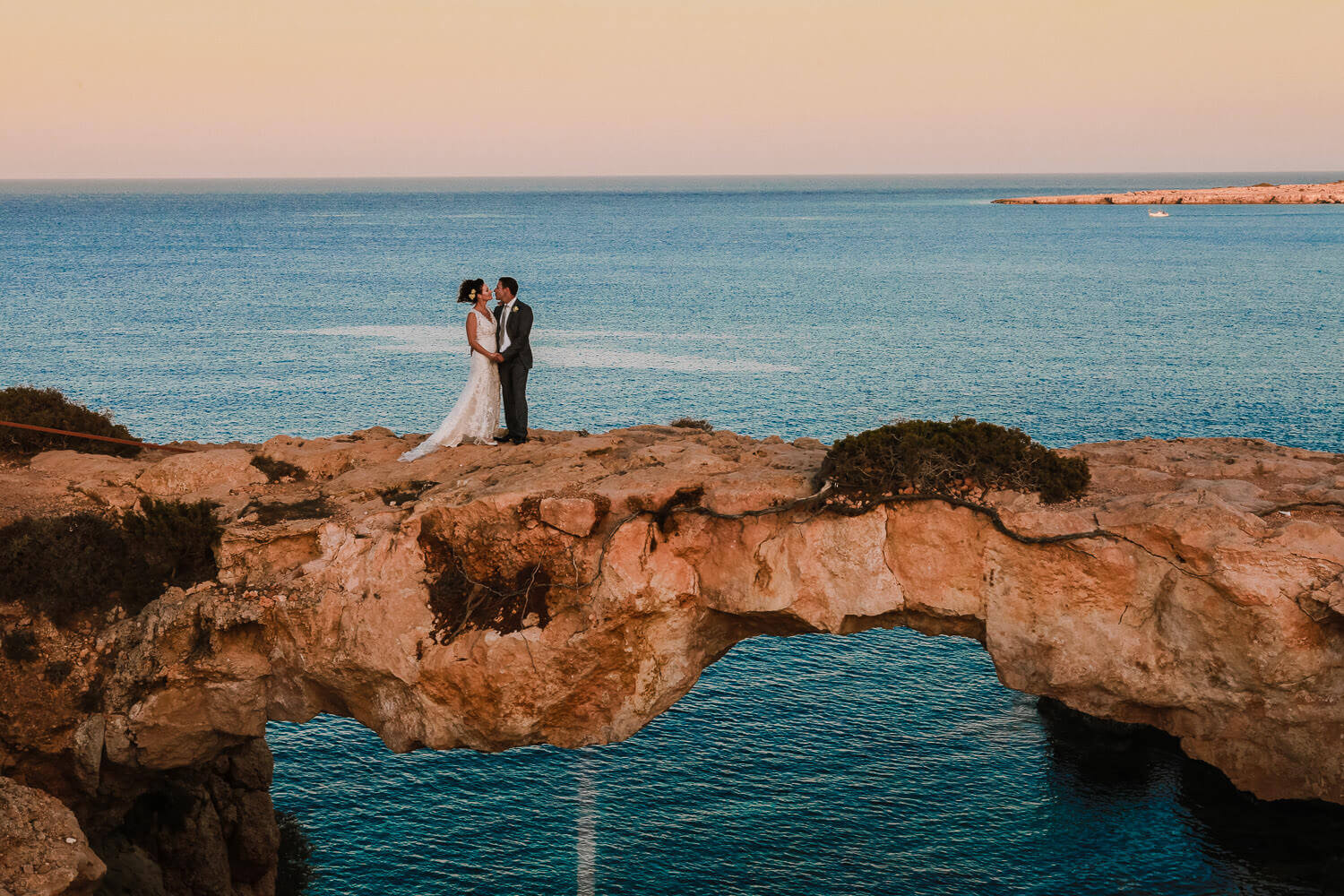 Epic photo of wedding couple standing on Cyprus love bridge, best wedding destinations in Europe