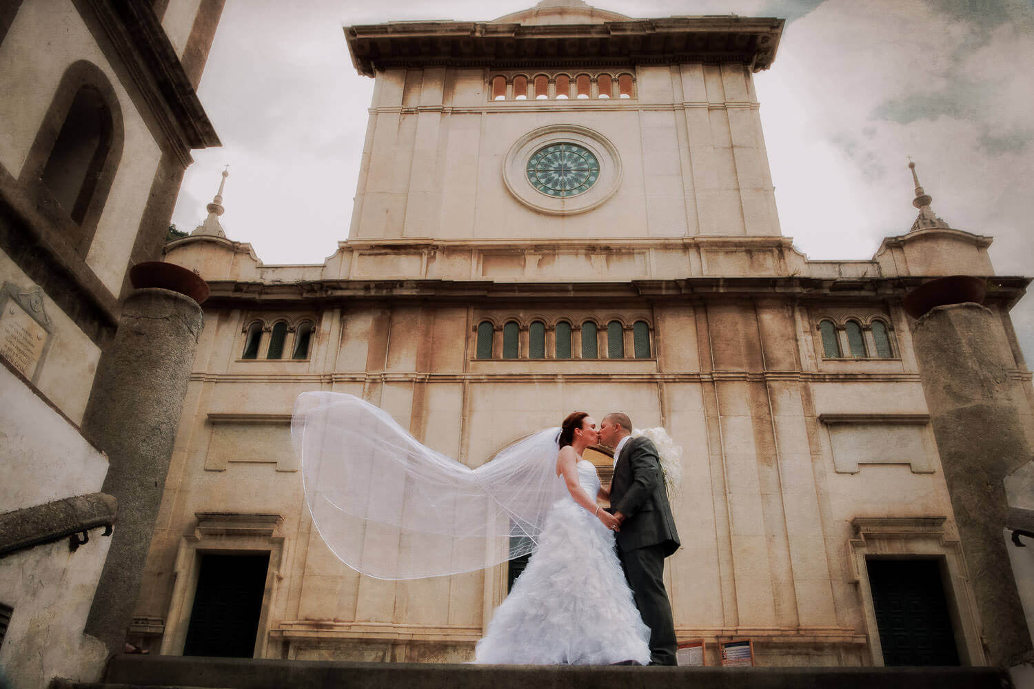 Romantic picture of bride and groom kissing Positano Church