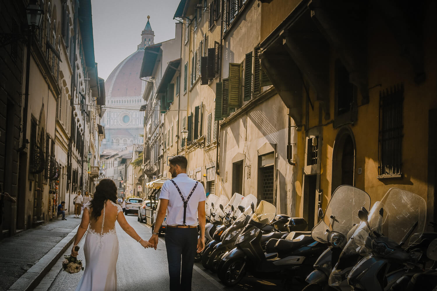 Bride and groom walking down back street in Florence