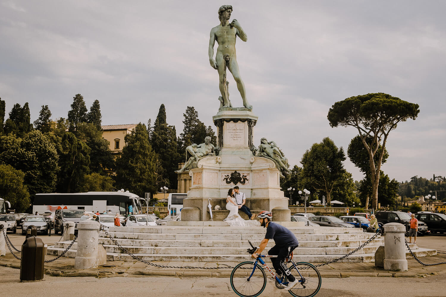 bride and groom sitting under David statue in Florence. Wedding photographer Wes Simpson