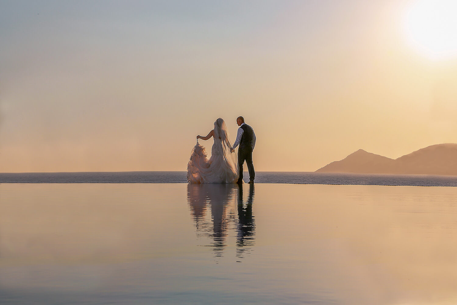 Silhouette bride an groom with reflection at sunset Liberty Lykia Hotels. Amazing wedding destination in Europe