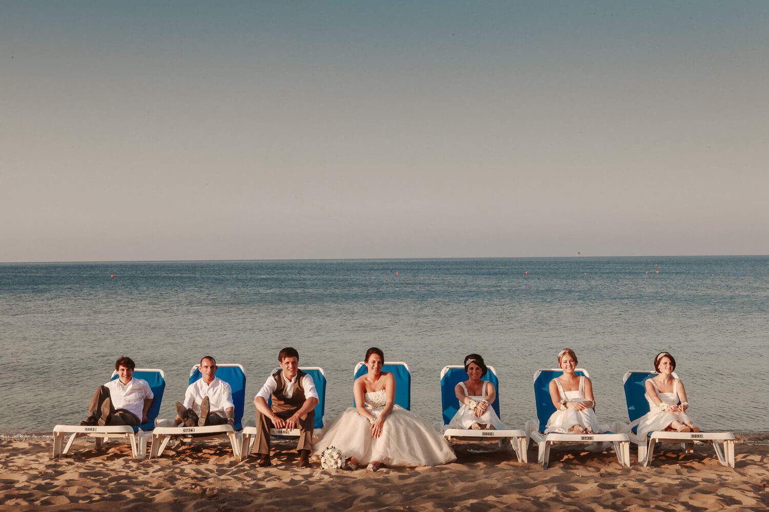 Bridal party on sun loungers at beach wedding Protaras Cyprus