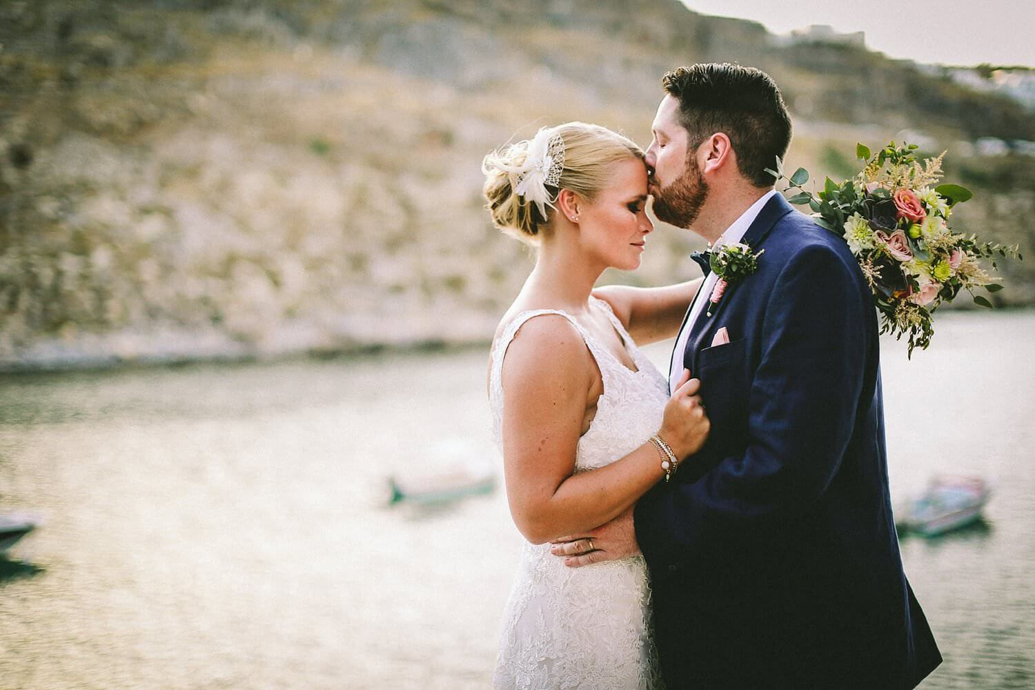 Groom kissing bride on head at sunset wedding St Pauls Bay Lindos