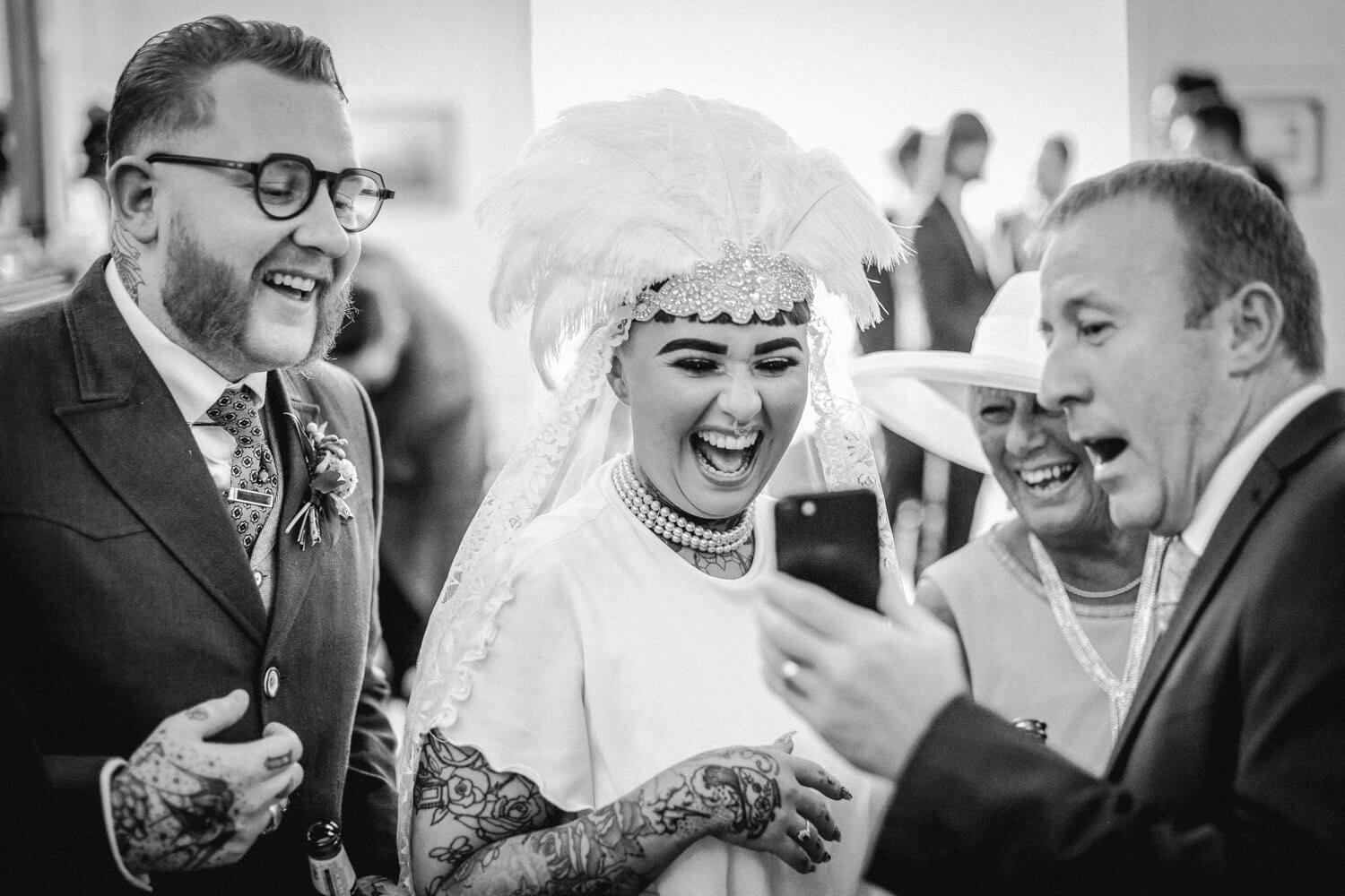 Vintage bride wearing head wear laughing at man showing whats on his phone at wedding Ashfield House