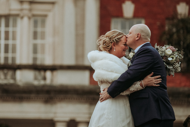 Groom kissing bride and head Eaves Hall wedding