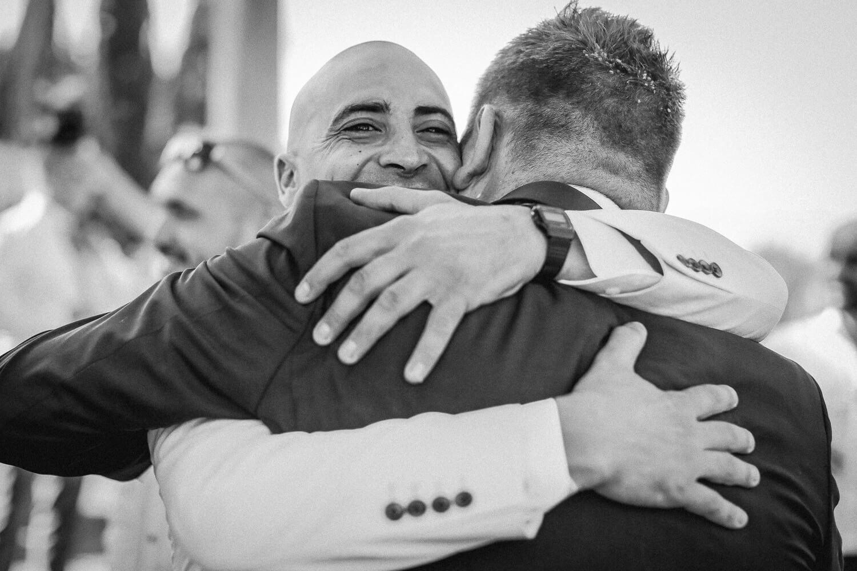 Two men hugging at wedding