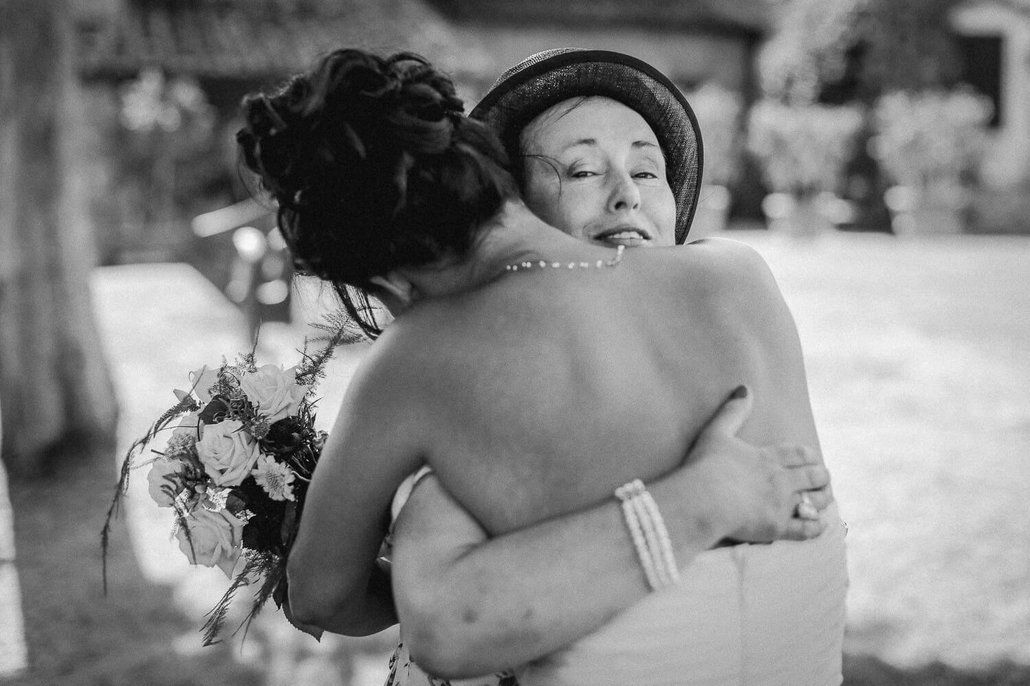 Two woman hugging at wedding