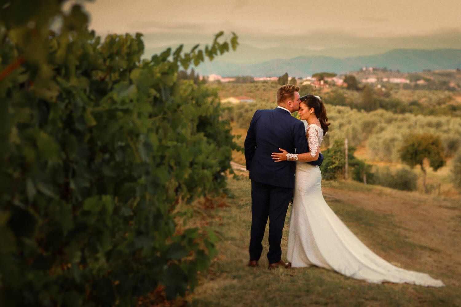 Bride and groom in Tuscany vineyard at sunset