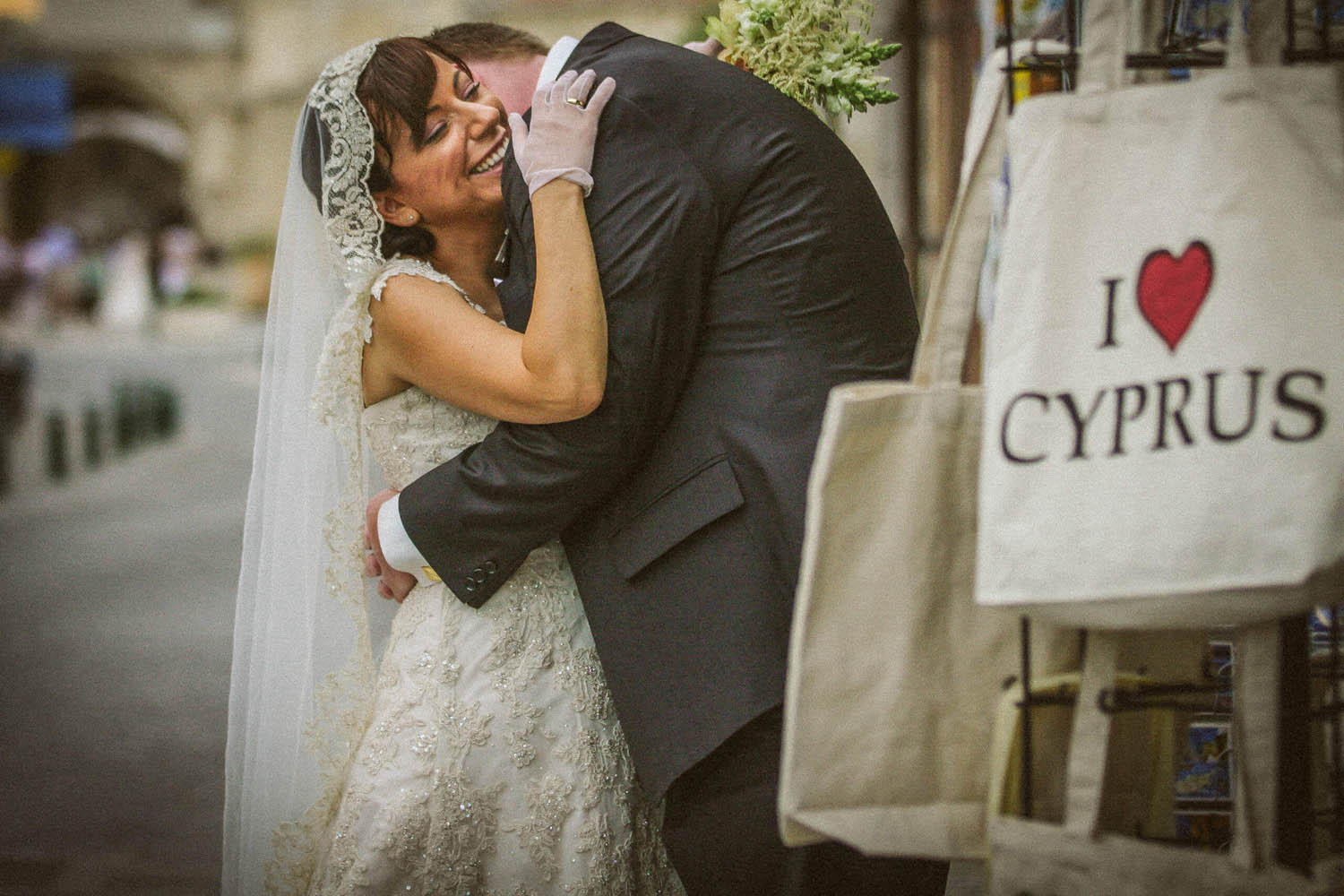 Bride hugging groom with sign on bag reading I love Cyprus