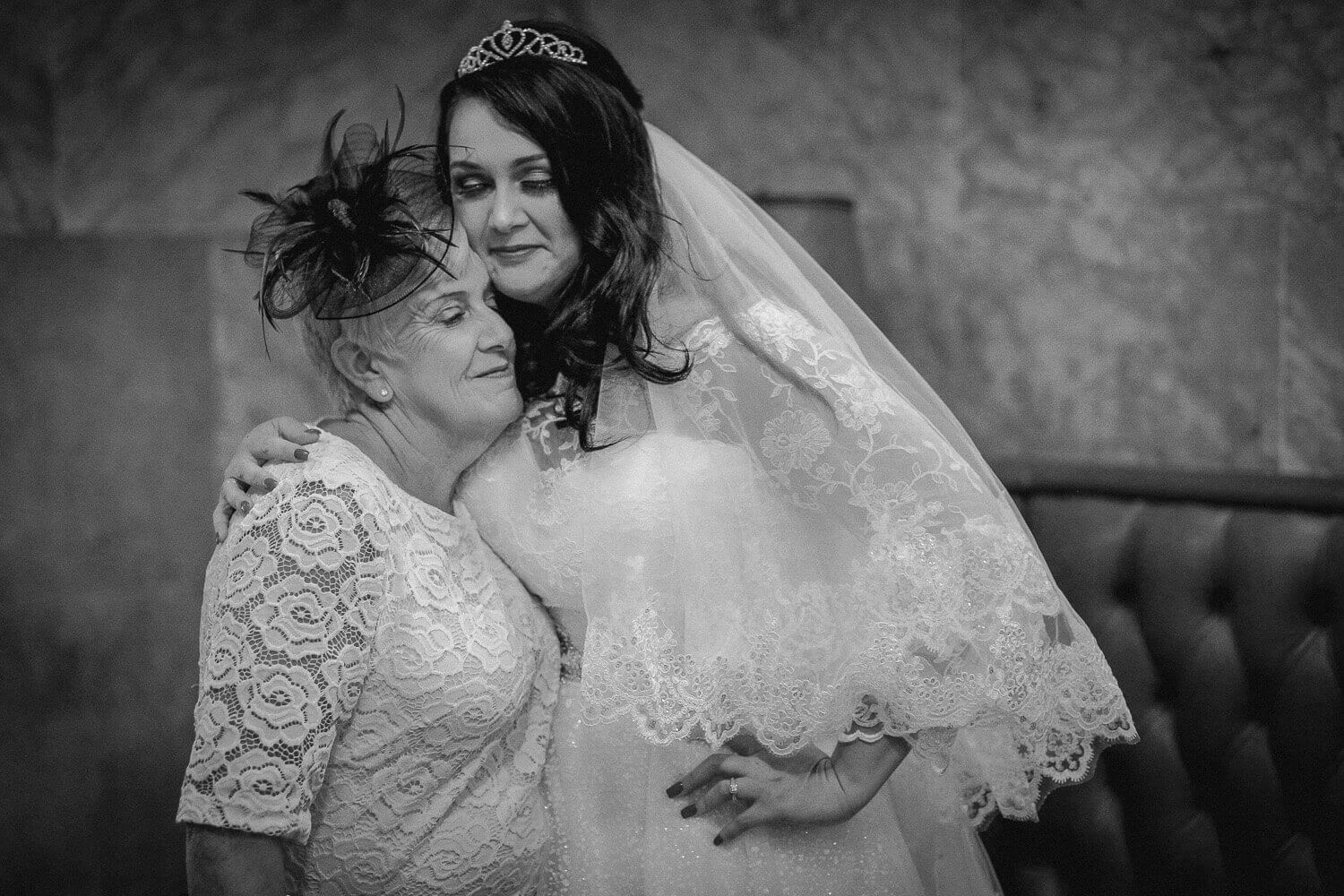 Bride in loving embrace with mother during a wedding in Liverpool