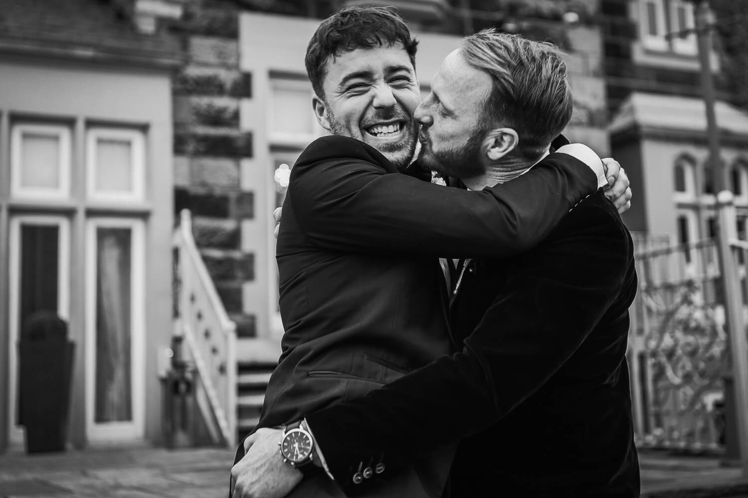 Two man hugging and kissing West Tower wedding