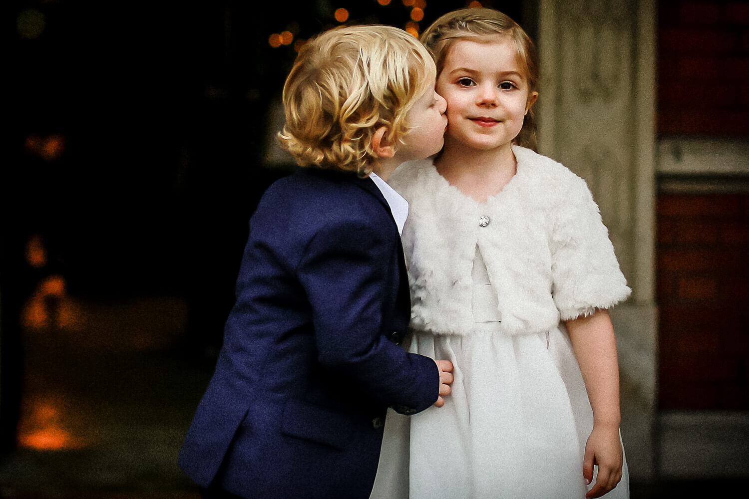 Little boy in blue suit kissing little girl at wedding Eaves Hall