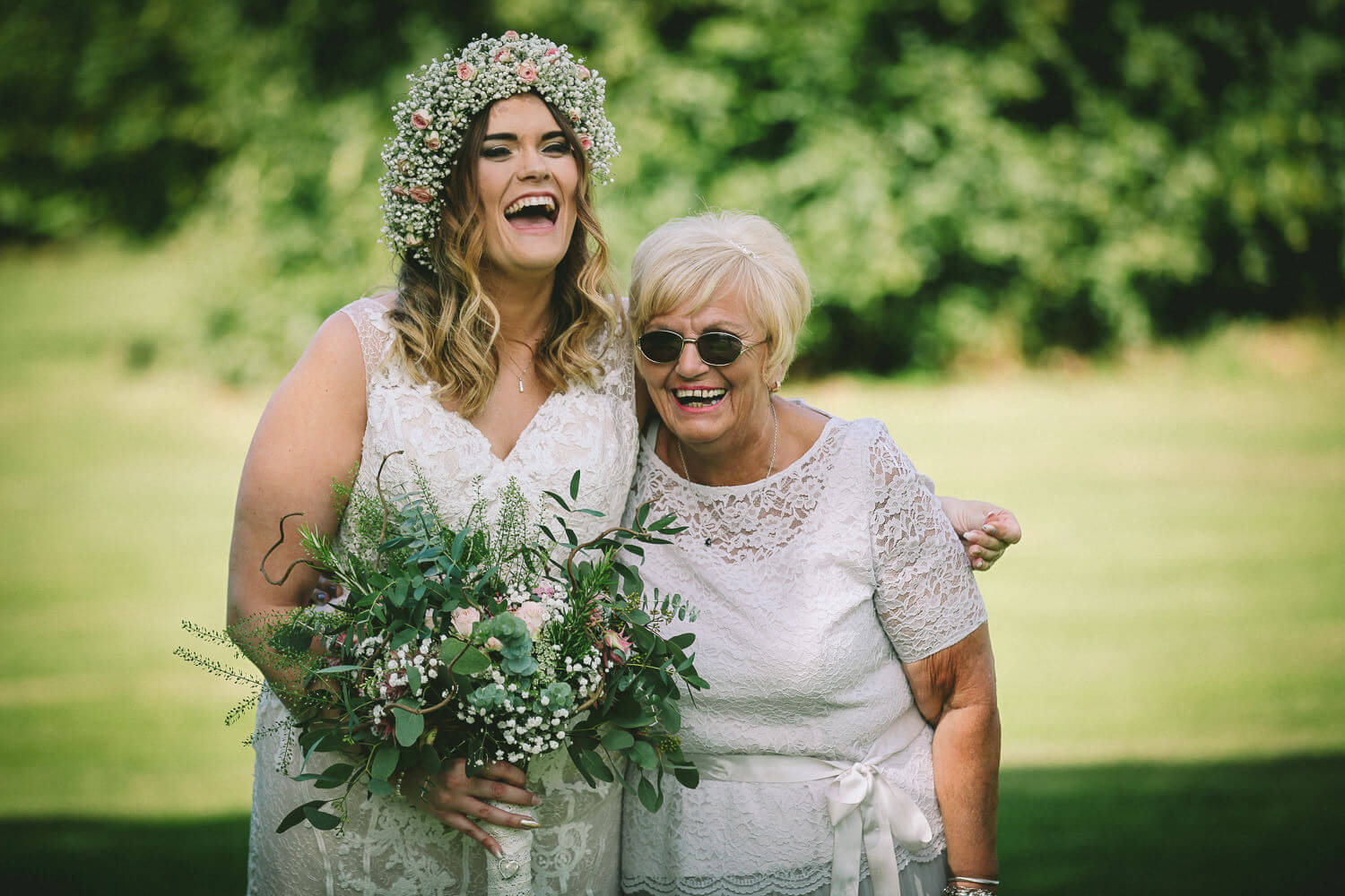 Bride with flowers in hair laughing with her mum on wedding day