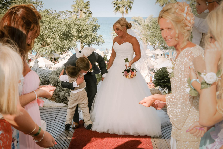 Little boy hugging bride and groom Sunshade beach hotel wedding