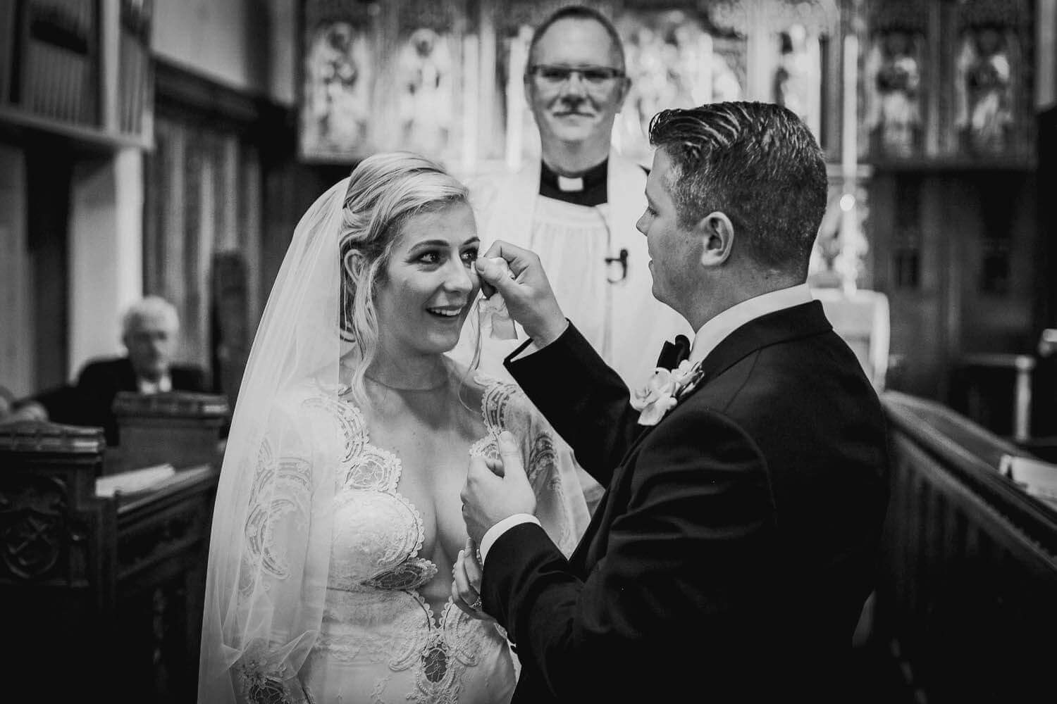 groom whipping tear from brides face in church