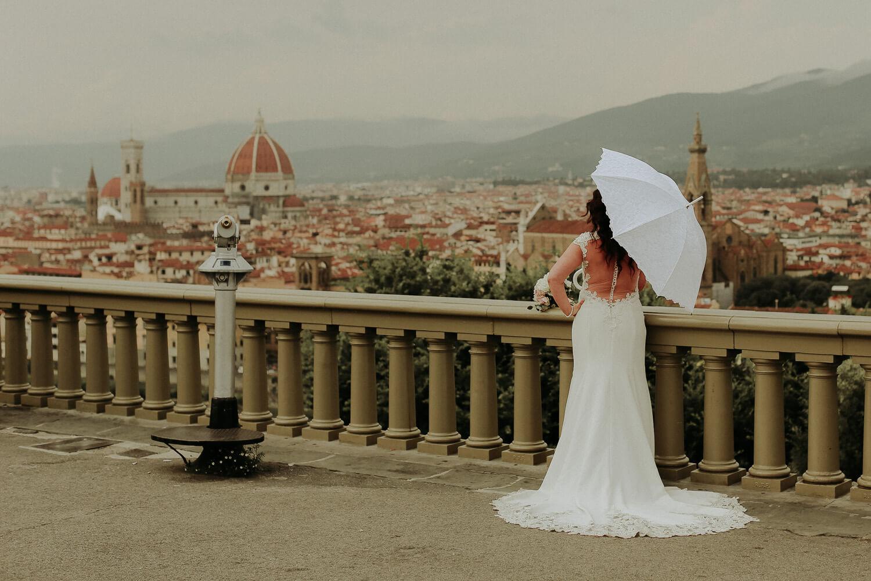 Bride with umbrella looking at Florence landscape. Tuscany wedding photographer UK