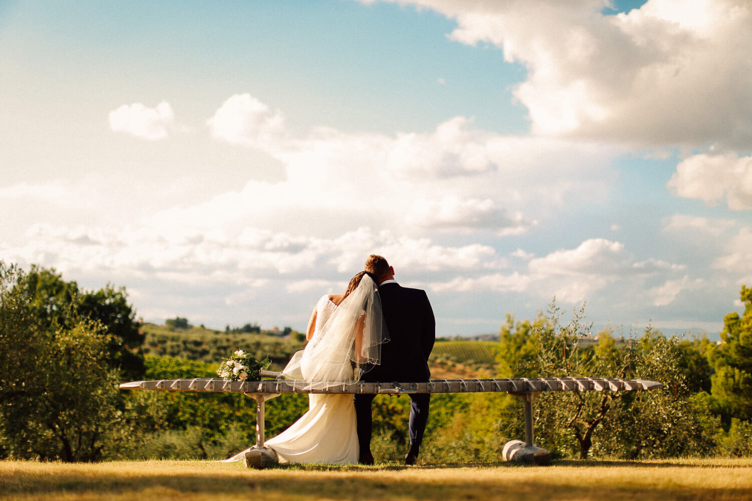 Bride and groom sitting in bench over looking Chianti hills. Tuscany wedding photographer UK