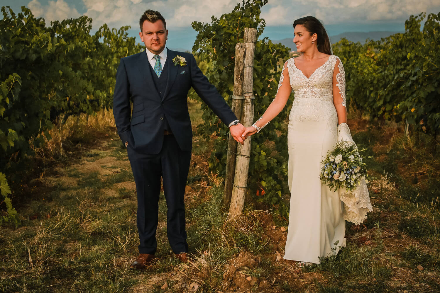 Bride and groom holding hands in vine yards. Tuscany wedding photographer UK