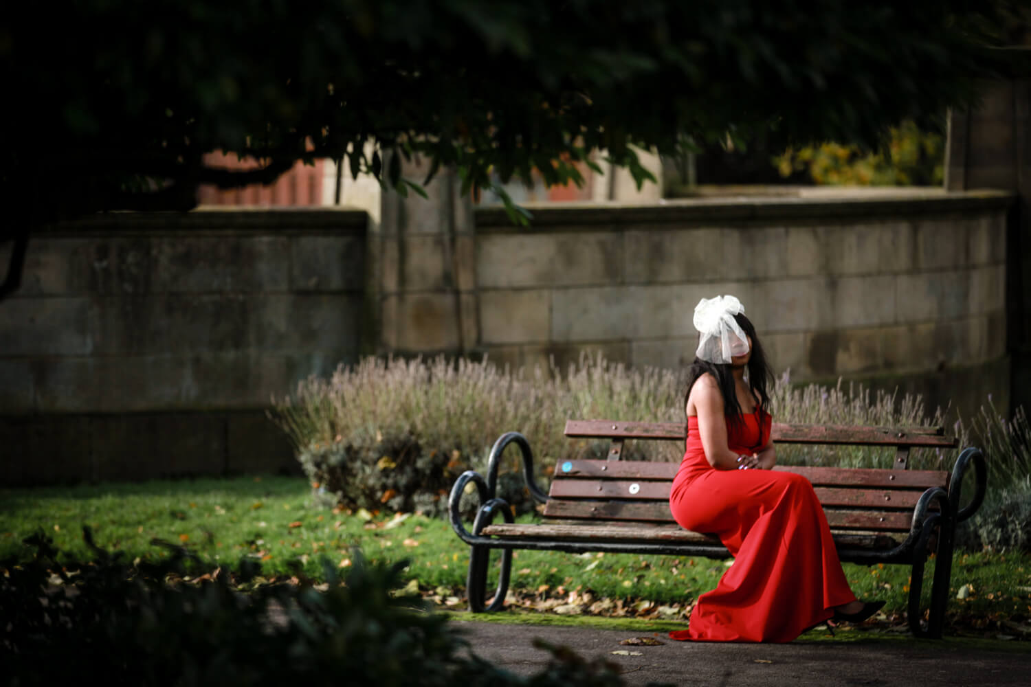 Bride in red dress sitting on bench Covid wedding Liverpool