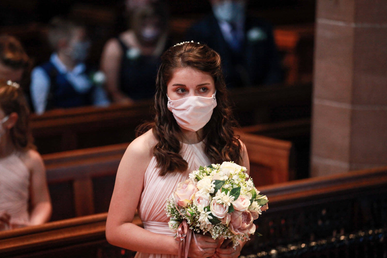 Bridesmaid wearing a mask in church at Covid wedding