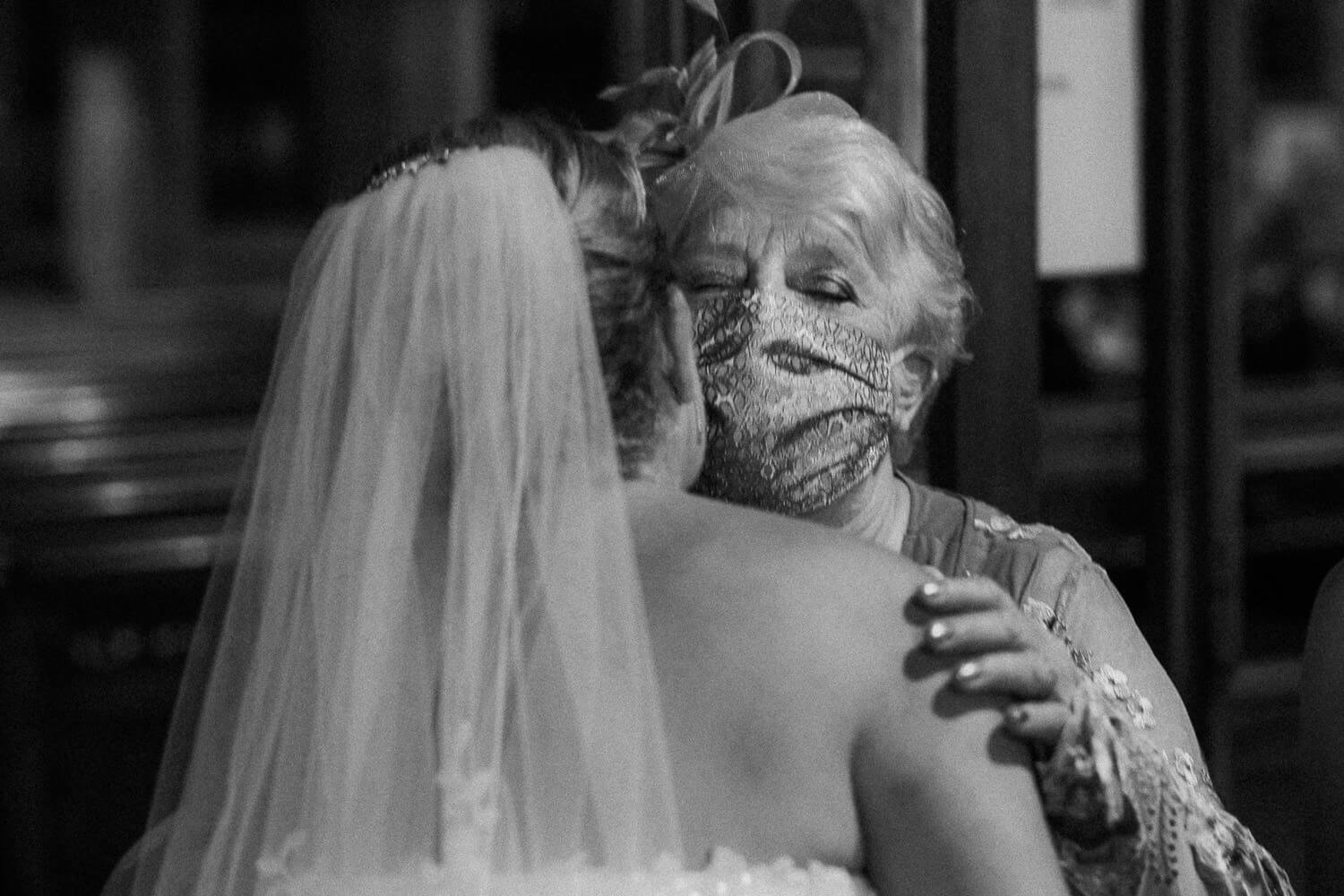 Woman hugging bride wearing a mask