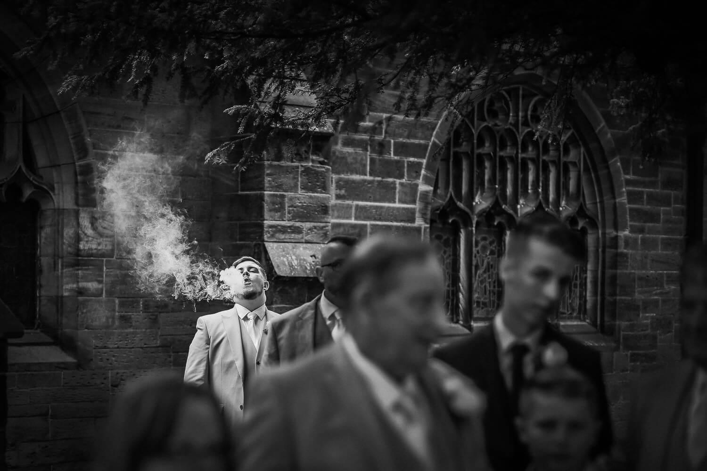 Man smoking outside church at wedding