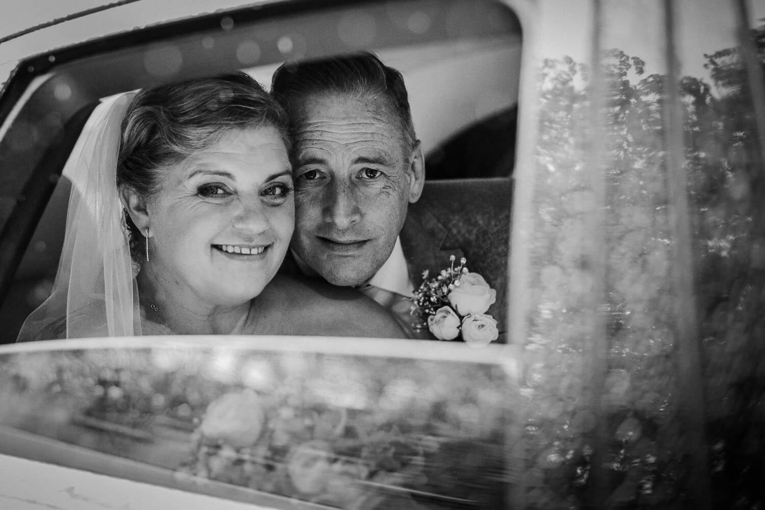 Black and white photo of bride and groom looking out of car window