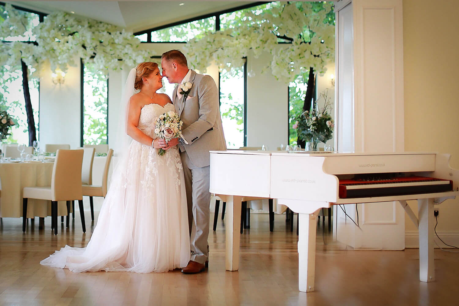 Bride and groom kissing next to white piano Covid wedding photography West Tower