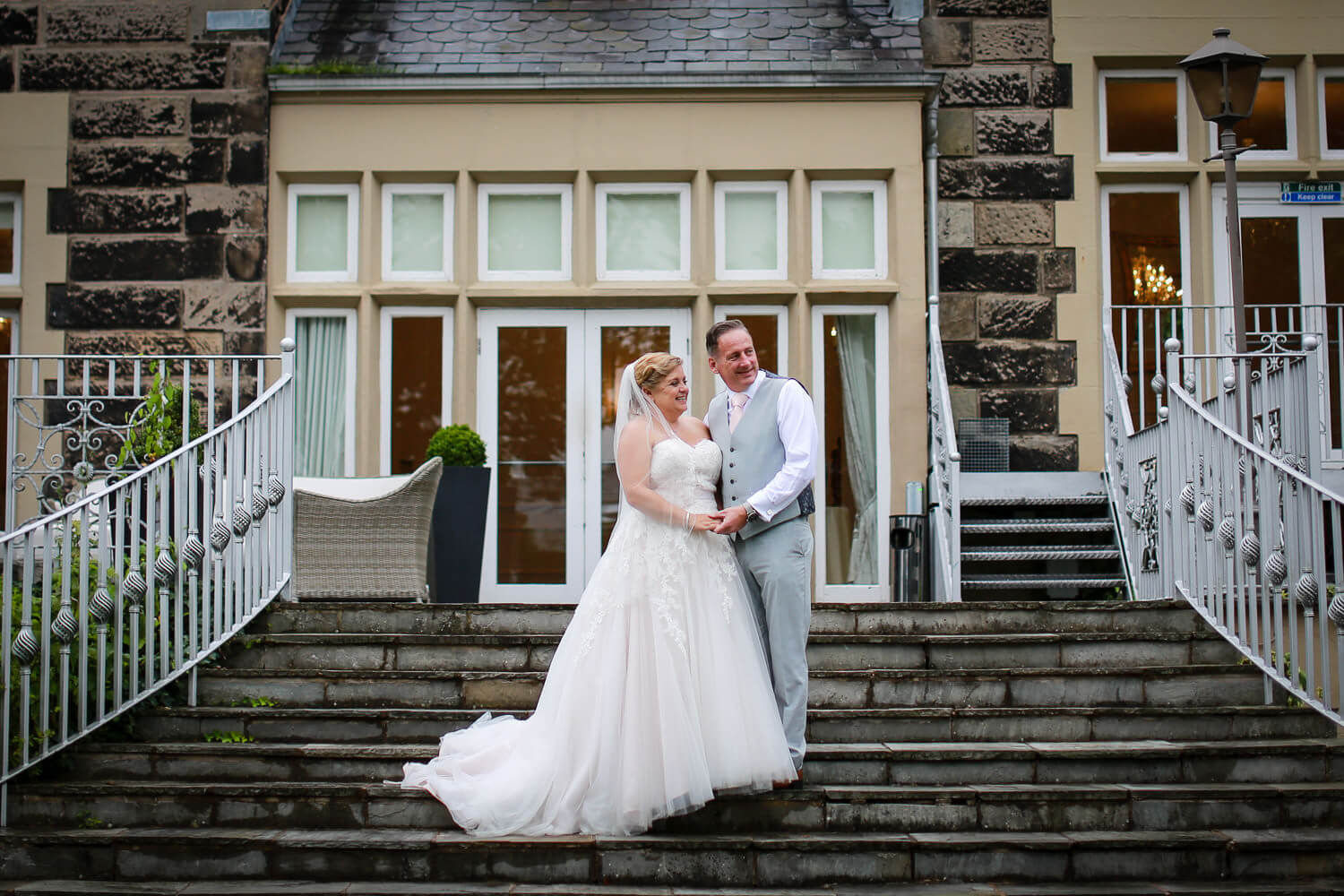 Bride and groom on steps of West tower wedding venue