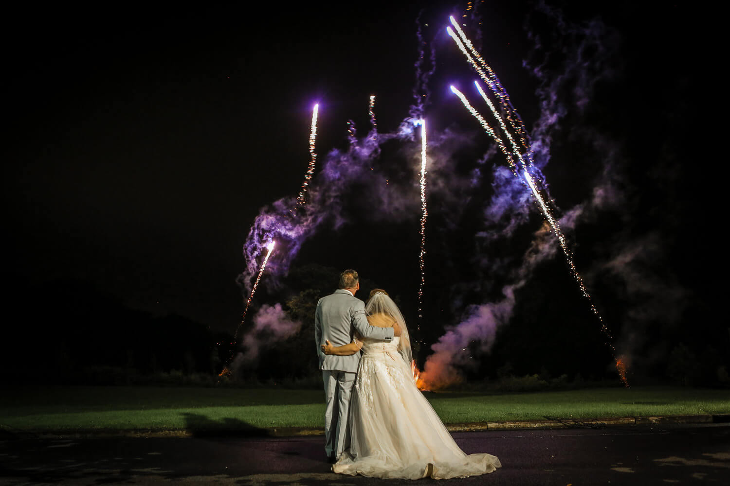 Bride and groom watching fireworks at West Tower
