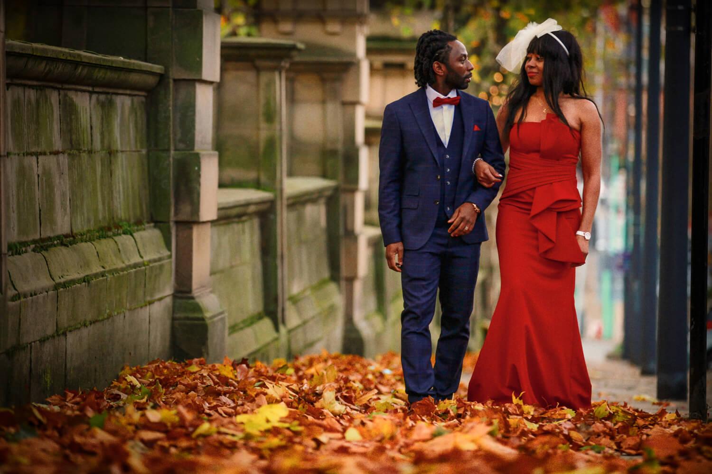 Emergency Covid Lockdown wedding Liverpool Bride and Groom walking through Autumn leaves